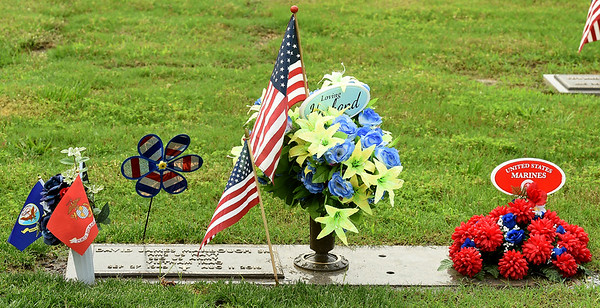 Patriotic tributes adorn the final resting place of U.S. Navy and Army veteran David James Marbough on Monday at Mount Hope Cemetery. Marbough served in both Vietnam and Iraq.<br /> Globe | Laurie SIsk
