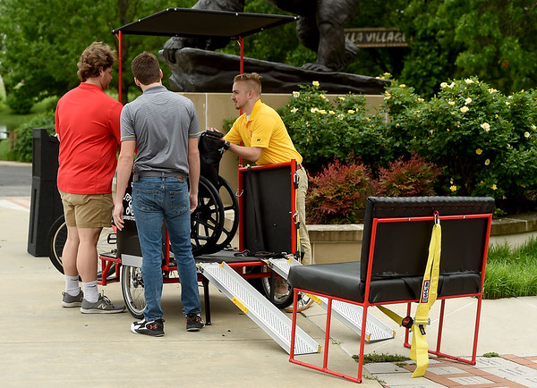 From the left: Pittsburg State University seniors Nick Haynes, trey Byrne and Mitchell Yeomans unload components of  the Mechanical and Manufacturing Engineering Technology's new Pedicab on Wednesday at Gorilla Village. The pedicycle allows volunteer pedalers in the Pittsburg community to give rides to wheelcgair bound persons and those with mobility challenges. Features include a cushioned bench, wheelchair, 500 lb. passenger capacity and telescopic wheelchair ramps.<br /> Globe | Laurie Sisk
