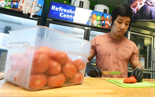 WorkFresh employee Reiden Tizon slices fresh tomatoes at the WorkFresh store on East Seventh Street on Friday. The business offers about 20 meal options using fresh ingredients.<br /> Globe | Laurie Sisk