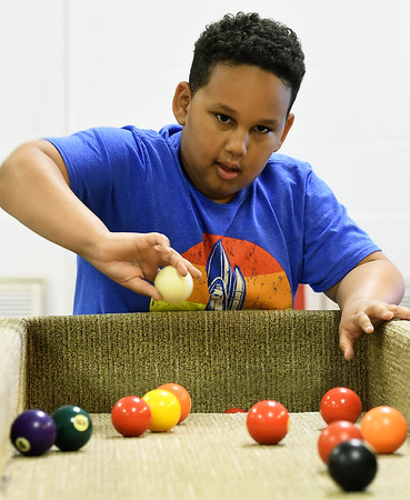 Nine-year-old Devaughn Fickle plays a game of carpetball during the afterschool program at the Boys and Girls Club of Southwest Missouri on Tuesday. <br /> Globe | Laurie Sisk