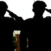 Cadets from Joplin High School JROTC are silhouetted as they salute the arrival of veterans before the start of Memorial Day ceremonies on Monday at Mount Hope Cemetery.<br /> Globe | Laurie Sisk