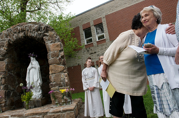 Georgiana McGriff, director of Joplin Area Catholic Schools, gives a hug to Carol Goff at the McAuley grotto on Thursday. The grotto is dedicated to Goff's late husband.<br /> Globe | Roger Nomer