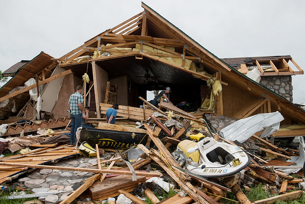 Friends and family helps clean up tornado damage on the Hughes' property, south of Wheaton, on Wednesday.<br /> Globe   Roger Nomer