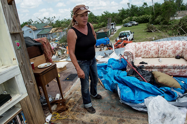 Laura Erickson looks over the second floor of her house after a tornado took its roof along Joplin Road outside Carl Junction on Friday.<br /> Globe | Roger Nomer