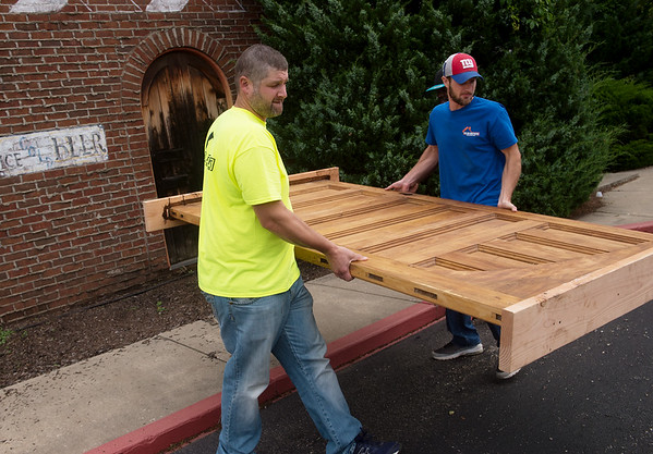 Robert (left) and Jeremiah Taylor, owners of Taylor Brothers Construction, carry one of the original Schifferdecker House doors at Del Rio on Thursday.<br /> Globe | Roger Nomer