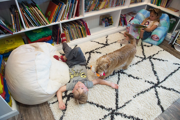 Four-year old Gideon Basye plays in the family's rebuilt library with dog Benji and seven-year old sister Maxx on Thursday in Carl Junction. Globe | Roger Nomer