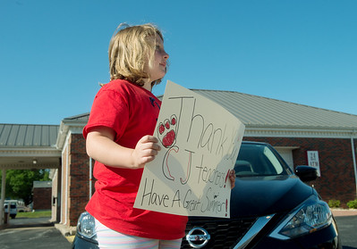 Nine-year old Iliana Tharp holds a sign for Carl Junction staff and teachers during a bus parade to mark the last day of school in Carl Junction on Thursday. Globe   Roger Nomer