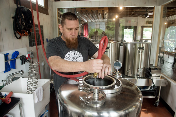 Eric Beezley cleans out a fermenter at Flag City Brewery in Webb City on Thursday.<br /> Globe   Roger Nomer