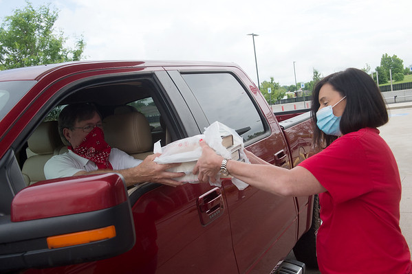 William Cannon picks up books from Eden Elliott, circulation supervisor at the Joplin Public Library, during the library's curbside pick up service on Wednesday. The Joplin Public Library recently announced they hope to reopen to the public on June 8 with limited hours. Globe | Roger Nomer