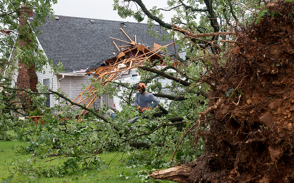 A volunteer helps clear trees from Isaiah Basye's house in the Briarbrook neighborhood of Carl Junction on Thursday. Globe | Roger Nomer