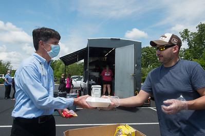 Morgan Watts (left), a physical therapist at Mercy Hospital Joplin, picks up lunch from Danny Murphy, a driver at Metro Towing, on Thursday at the hospital. To honor hospital nurses and staff, Metro Towing and Ghetto Tacos provided free food throughout the day for Mercy employees. Globe   Roger Nomer