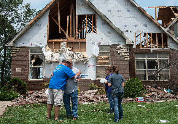 Homeowner Keith James, center, gets a hug from friend Clive Veri, left, after friends and family helped him move furniture from his tornado-damaged house in the Briarbrook neighborhood of Carl Junction on Thursday. Globe   Roger Nomer