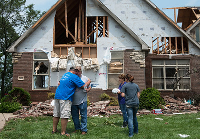 Homeowner Keith James, center, gets a hug from friend Clive Veri, left, after friends and family helped him move furniture from his tornado-damaged house in the Briarbrook neighborhood of Carl Junction on Thursday. Globe | Roger Nomer