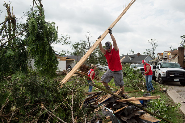 (from left) Alexis Lawhead, Tug Baker and Josh Hayes, from Lowe's Home Improvement in Carthage, clean debris in Briarbrook on Friday. Globe | Roger Nomer