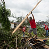 (from left) Alexis Lawhead, Tug Baker and Josh Hayes, from Lowe's Home Improvement in Carthage, clean debris in Briarbrook on Friday.<br /> Globe | Roger Nomer