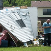 Isaiah Basye checks in with his insurance company following tornado damage to his house in the Briarbrook neighborhood of Carl Junction on Thursday.<br /> Globe | Roger Nomer