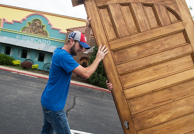Jeremiah Taylor, co-owner of Taylor Brothers Construction, lifts one of the original Schifferdecker House doors at Del Rio on Thursday. Globe | Roger Nomer