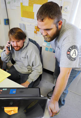 Globe/T. Rob Brown<br /> AmeriCorps St. Louis Joplin Recovery Project leaders Chad Angell, right, project team leader, and Cameron Coe, volunteer coordinator, work on their daily paperwork Thursday afternoon, Nov. 29, 2012, in the organization's Joplin office on School Street.