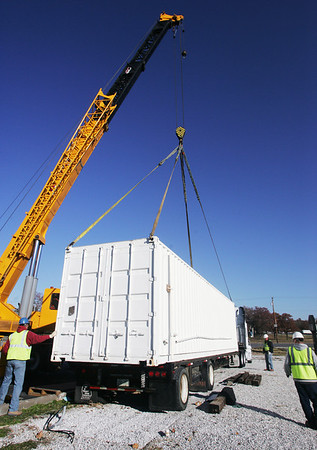 Globe/Roger Nomer<br /> A crane lifts a mobile medical center onto a flatbed trailer at Joplin Family Worship Center on Thursday.