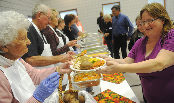 Globe/Roger Nomer<br /> Kathleen Cupp, Joplin, left, gives a plate to Cindy Morgan, Alba, during the Thanksgiving meal at First United Methodist Church.