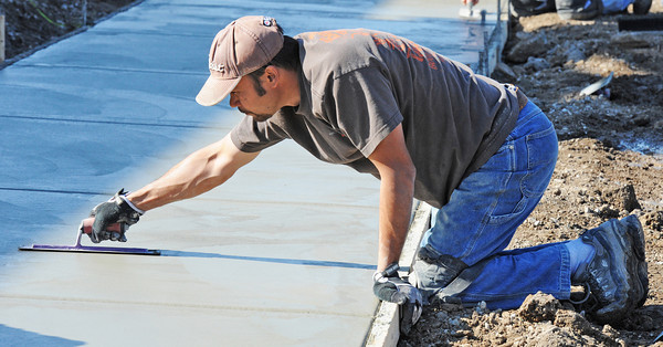 Globe/T. Rob Brown<br /> Jay Gallagher of Joplin and a concrete finisher with Cal Construction of Kansas CIty, Kan., smooths concrete for the sidewalk outside Taco Bell on South Main Street in Joplin Friday afternoon, Nov. 16, 2012. The Taco Bell was destroyed during the May 22, 2012, tornado.