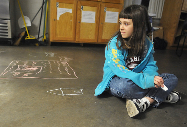 Globe/Roger Nomer<br /> Sami Valdez, 8, pauses after drawing a chalk house on the floor of CHOICES Emergency Shelter in Pittsburg on Thursday, Nov. 15, 2012.  Valdez's family hopes to soon transition to an apartment, and then a house, in the near future.