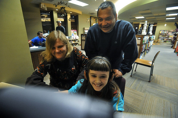 Globe/Roger Nomer<br /> Karey, Pat and Sami, 8, Valdez laugh while playing an online computer game at the Pittsburg Public Library on Thursday, Nov. 15, 2012.  The family often visits the library in the evening for entertainment.