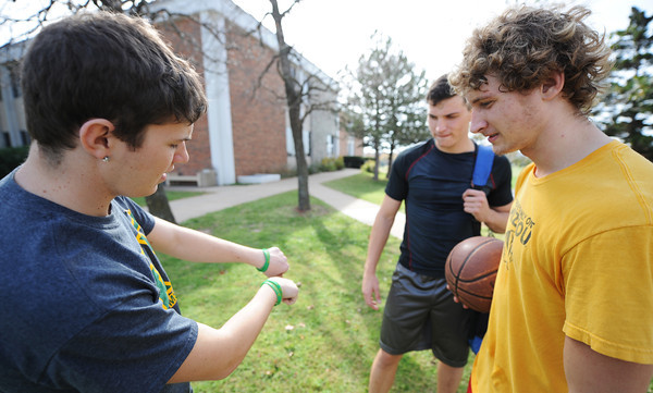 "Globe/T. Rob Brown<br /> Jarrett Epperson, left, a sophomore general business major at MSSU and a member of the Kappa Sigma fraternity, shows off his green ""Beat Pitt State"" arm bands to fellow sophomores Shane Hammond, right, undecided major, and Dustin Cates, biology major, Friday afternoon, Nov. 2, 2012, on the campus oval. Epperson was selling the bracelets on behalf of Kappa Sigma to promote the upcoming MSSU-PSU game as well as to make money for a charitable organization."