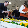 Globe/T. Rob Brown<br /> Dr. Bruce Speck, left, president of Missouri Southern State University, serves cupcakes and pieces of cake to Heather Arnold, center, director of aquatics & wellness, and Rikki Smith with the Resource Development Center, in honor of the 75th day of MSSU's 75th anniversary, Tuesday afternoon, Nov. 13, 2012, at Billingsly Student Center.