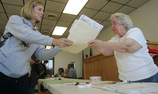 Globe/Roger Nomer<br /> Katie Miller, Galena, receives a ballot from Sally Hughes at Galena City Hall on Tuesday morning.