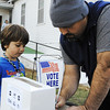 Globe/T. Rob Brown<br /> Matthew Ferguson, of Silver Creek, fills out an exit poll as his five-year-old son, Zoran Ferguson, looks on Tuesday afternoon, Nov. 6, 2012, outside the Saginaw Baptist Church polling location.