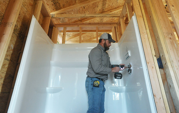 Globe/Roger Nomer<br /> Eric Jeffries installs a shower fixture at 2630 Wall on Tuesday morning.