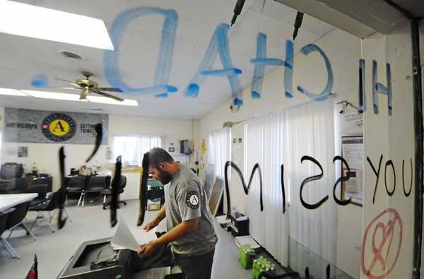 Globe/T. Rob Brown<br /> AmeriCorps St. Louis Joplin Recovery Project Team Leader Chad Angell works on his daily paperwork Thursday afternoon, Nov. 29, 2012, in the organization's Joplin office on School Street. A former AmeriCorps team member, who finished their term of service in Joplin, wrote a goodbye message to Angell on the window next to his desk.