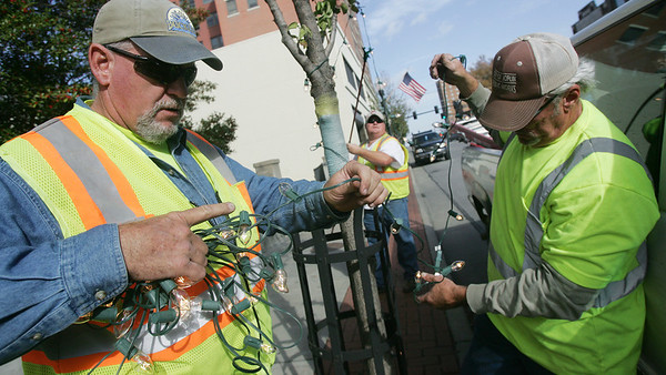 Globe/Roger Nomer<br /> (from left) Larry Block, Mark Hedrick and Jeff Wilks untangle Christmas lights as they decorate downtown Joplin on Friday morning.