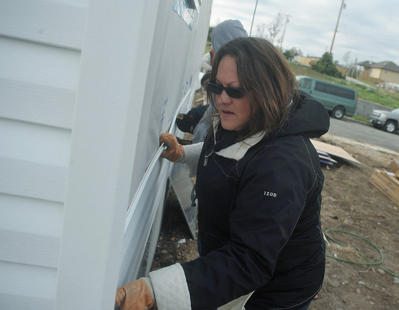 Globe/Roger Nomer<br /> Angela Kunce works on siding her home at 2630 Wall during a recent work day at the site.