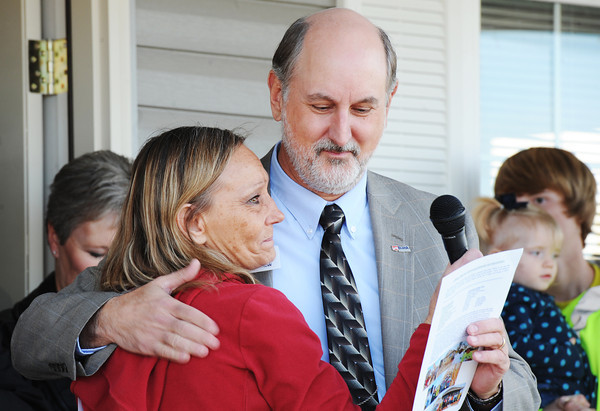 Globe/T. Rob Brown  Richard Crow with Joplin Area Habitat for Humanity, gets a hug from Linda Hazley, one of five families which will soon be moving into homes built through the Governor's Joplin Challenge in cooperation with Habitat and the Kansas City Chiefs in front of Norma Taylor's home Tuesday afternoon, Nov. 13, 2013, in the 2600 block of Kentucky Avenue. The five families include: Taylor, Wayne and Jamie Crandell, Amy Stockton, Hazley and Laurence and Marchella Claar.