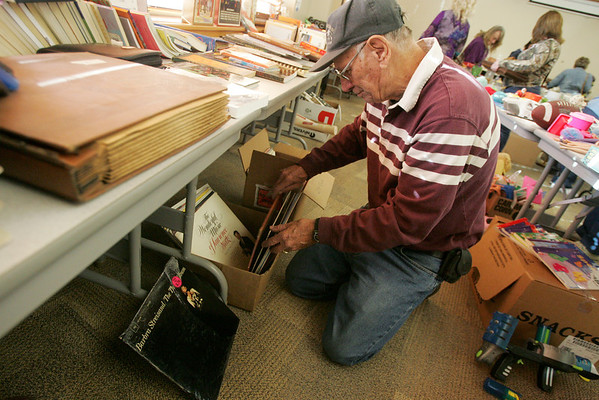 Globe/Roger Nomer<br /> Don Hodson, Joplin, looks through albums at the Wildcat Glades Rummage Sale at the Wildcat Glades Conservation & Audubon Center on Friday morning.  The sale continues today, with proceeds going to benefit the nature center.