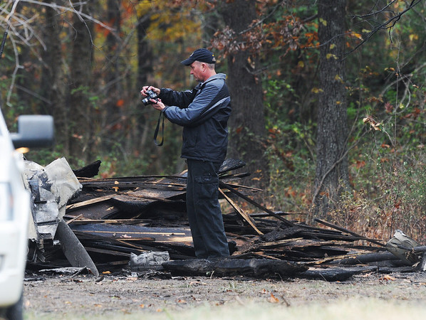 Globe/Roger Nomer<br /> An investigator takes photos of plane wreckage west of Stotts City on Monday afternoon.