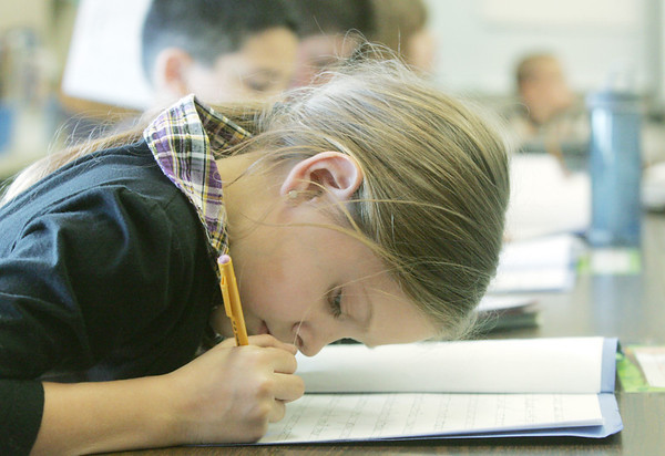 Globe/Roger Nomer<br /> Mia Jasinski, third grade, concentrates on looping her letters together during class at Columbia Elementary on Wednesday.