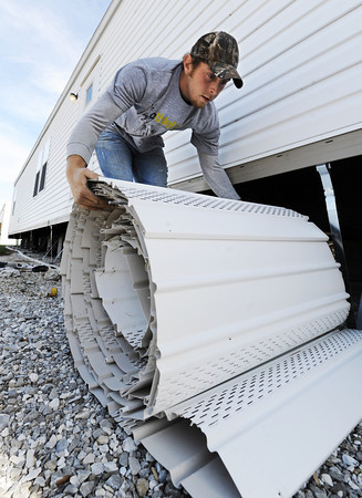 Globe/T. Rob Brown<br /> Brandon Brewer of Joplin, maintenance with Riley Mobile Homes of Joplin, removes the skirt from a FEMA mobile home Thursday morning, Nov. 29, 2012, at the mobile home park across from the Joplin Regional Airport.