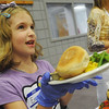 Globe/Roger Nomer<br /> Emma Sitton-Coats, 7, hands out plates to visitors at First United Methodist Church on Thursday.