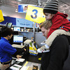 "Globe/T. Rob Brown<br /> Two-year-old Ace Kirkpatrick looks on with tired eyes from atop the shoulders of his father, Reid Kirkpatrick, both of Joplin, pays Naomi Negron, sales transaction assistant, for computer memory Friday morning, Nov. 23, 2012, during Black Friday sales at Best Buy. ""Not bad,"" Kirkpatrick said of the sale. ""Half price."" The Kirkpatricks had been up all night at various sales and Ace Kirkpatrick agreed he was ready for bed."