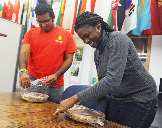 Globe/Roger Nomer<br /> Yezeed Aldhwayan, a Pittsburg State junior from Saudi Arabia, and Kanwulia Amoye, a Pittsburg State grad student from Nigeria, unwrap pumpkin pies in preparation for a Thanksgiving meal.
