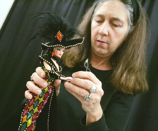 Globe/Roger Nomer<br /> Toni LoPresti works with Masquerade Barbie from the Bob Mackie collection while setting up a display at Joplin City Hall. LoPresti said the Masquerade Barbie is her favorite doll in her vast collection.