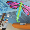 Globe/Roger Nomer<br /> A dragonfly kite hangs in the hallway of Irving Elementary as Nathan Osborn, with Pinnacle Signs, works on a collar for abstract trees on Wednesday.