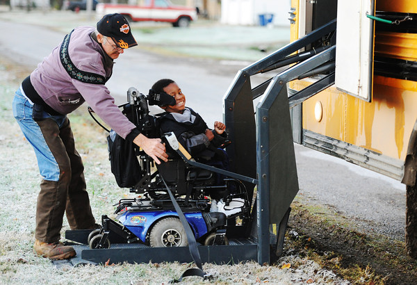 Bus driver Mike Meyer helps John Workman, a student with special needs, get onto a school bus in McCune, Kan., recently for the Cherokee County School District, USD 247.<br /> Globe | T. Rob Brown
