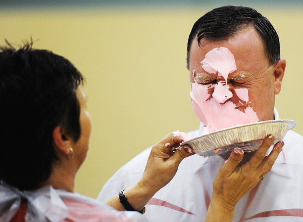 Dr. Phil Cook, Carl Junction School District superintendent, takes a pie to the face from Carl Junction Postmaster Sharon Clark Wednesday morning, Nov. 6, 2013, at the Carl Junction Community Center gymnasium. The event was in recognition of the Carl Junction post office selling the most breast cancer awareness stamps in the nation.<br /> Globe | T. Rob Brown