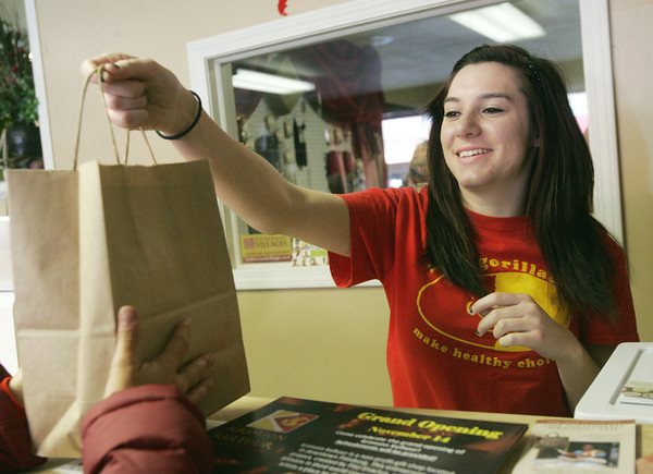 Globe/Roger Nomer<br /> Ashton Halda, a Pittsburg State sophomore from Spring Hill, Kan., helps a customer during the grand opening of Krimson Kultuur on Thursday.