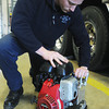 Globe/Roger Nomer<br /> Joplin Firefighter Ben Phillips checks a hydraulic pump at Joplin Fire Station One on Wednesday afternoon.