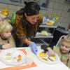Globe/Roger Nomer<br /> Tracy Eck, assistant teacher, serves Jacob Greer, 4, right, and Zeke Hymer, 5, a Thanksgiving meal at the First United Methodist Church preschool on Tuesday morning.